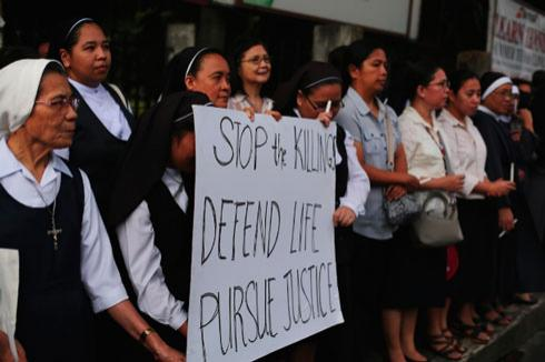 A group of nuns join a candle-lit demonstration in Manila to protest attacks against members of the clergy. (Photo by Jire Carreon)