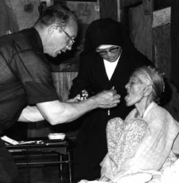 Fr Francis Royer SSC gives communion to an elderly Korean woman in 1972.