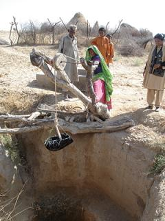 Family at the water well in Pakistan.