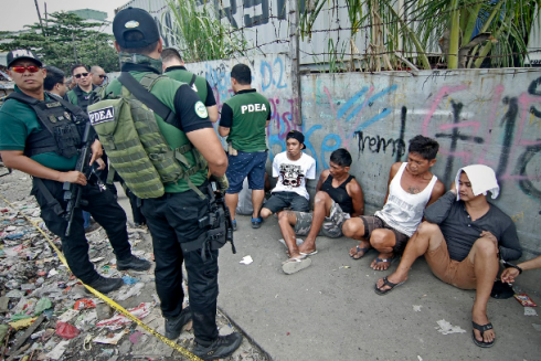 Philippine drug enforcement agents arrest suspected drug users and dealers in an urban poor community in Manila. (Photo by Vincent Go, UCANEWS)