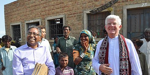(right) Columban missionary priest, Fr Robert McCulloch visiting the housing project for the homeless in Sindh, Pakistan, in 2015.